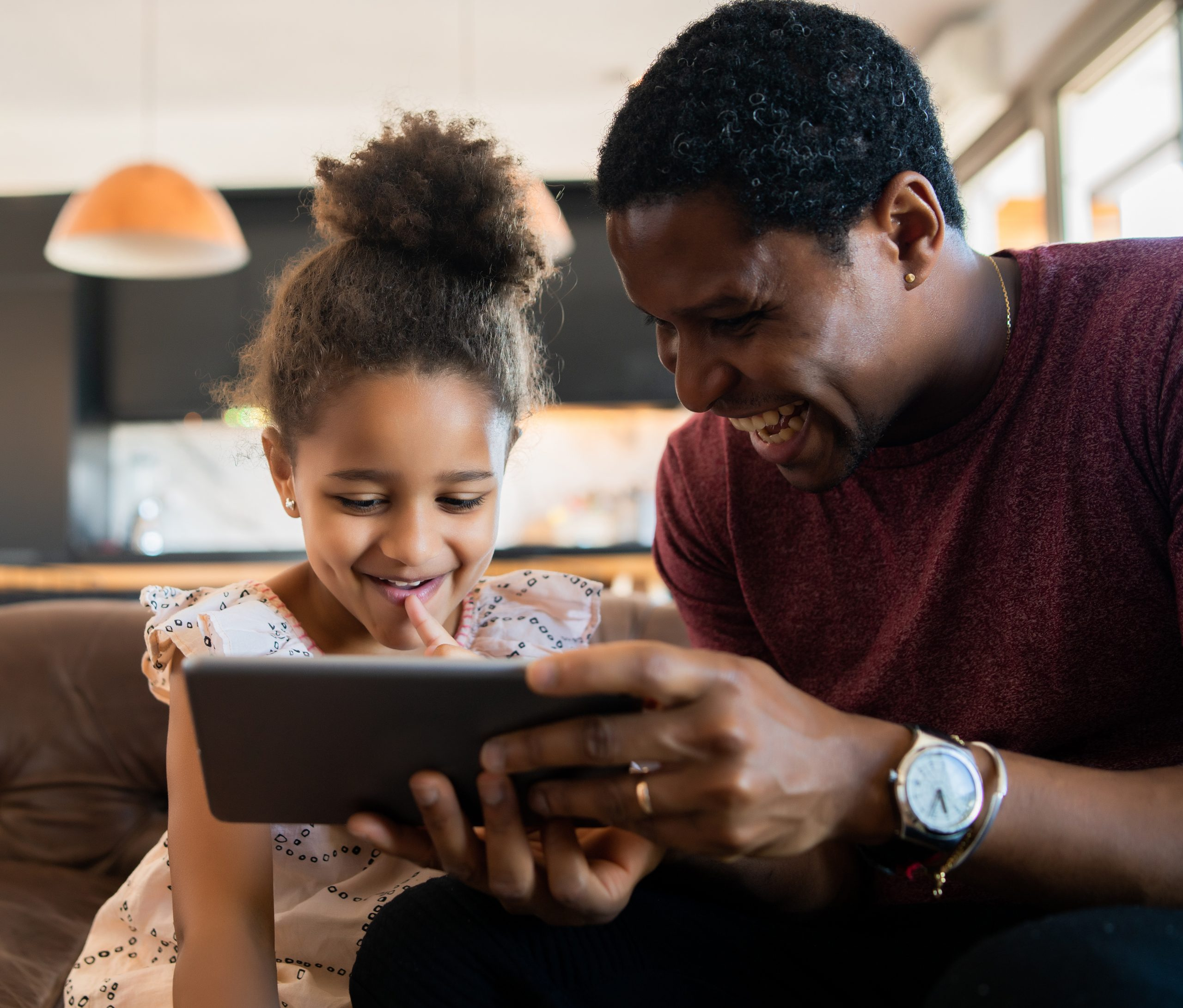 Father and daughter smiling and looking at device